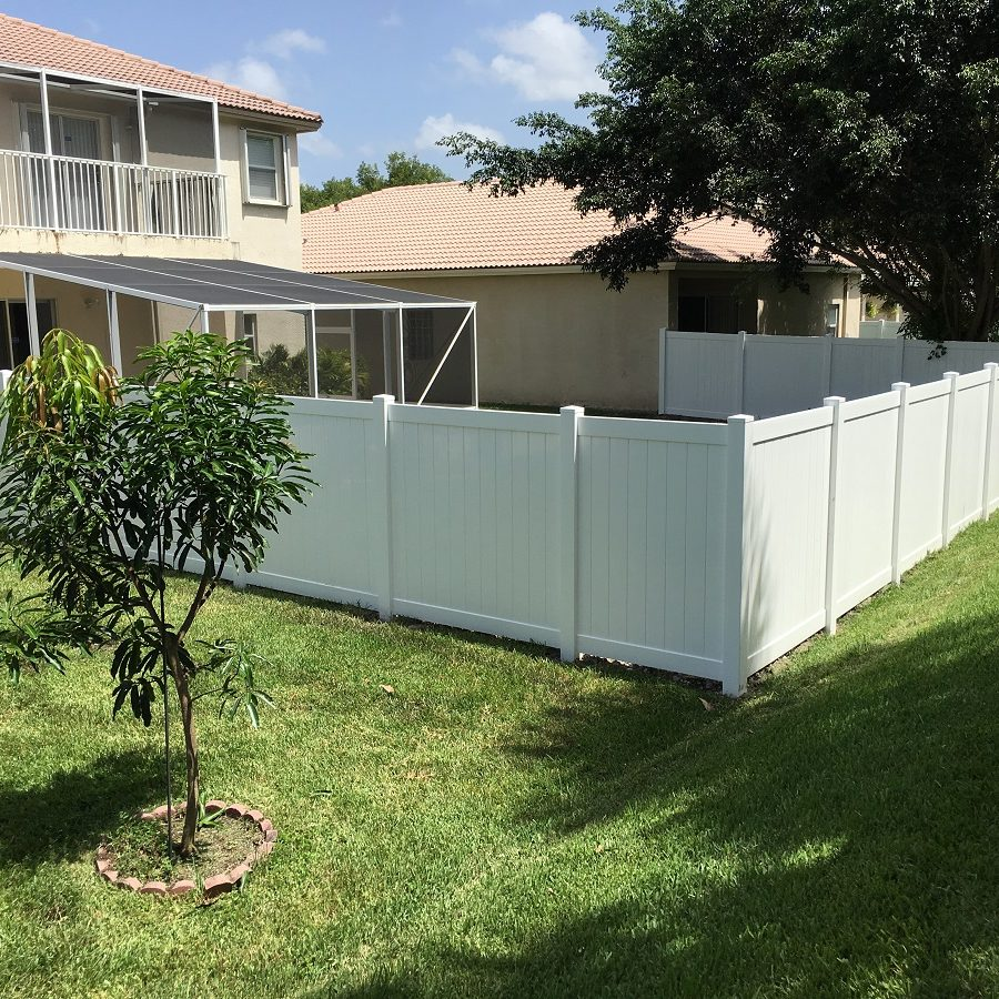 residential fence installation of a white pvc fence
